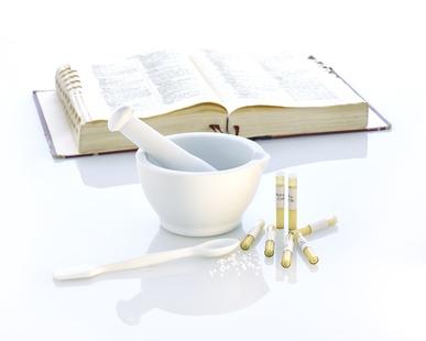 weißer Mörser mit Glasröhrchen Globuli und Buch